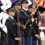 Soldiers in dress blues with U.S. flag